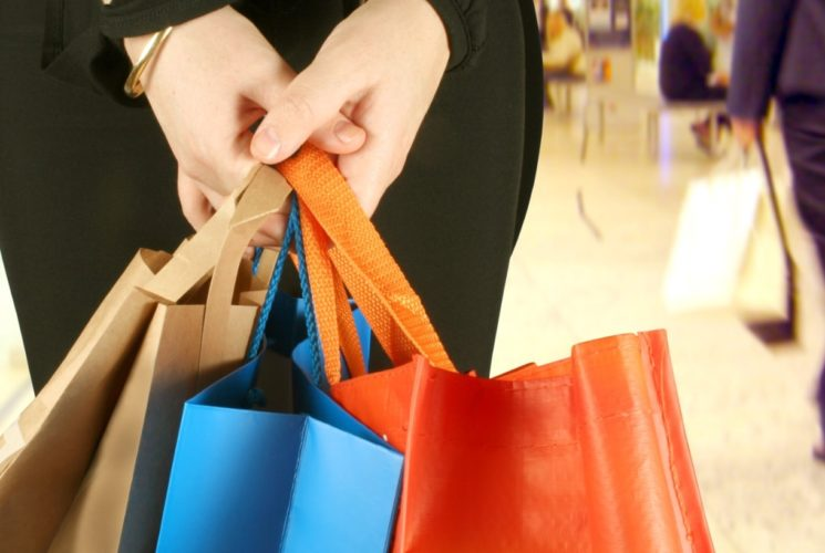 Person holding multicolored shopping bags