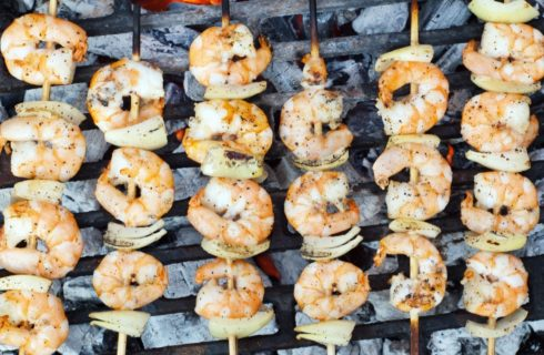 Skewers of shrimp and onions over hot coals