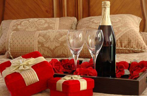 Wine glasses and bottle of wine in tray on bed