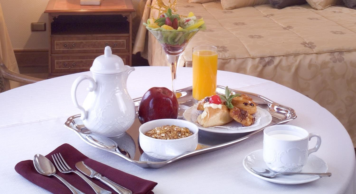 Silver tray with breakfast items on table with white tablecloth