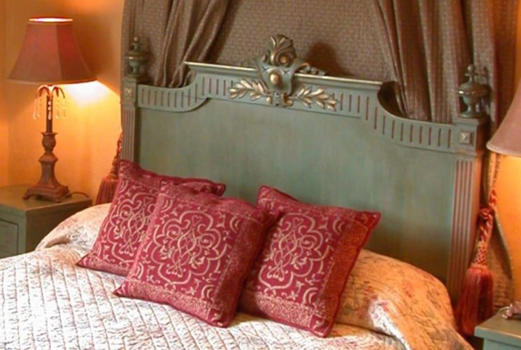 Green wooden headboard with multicolored bedding