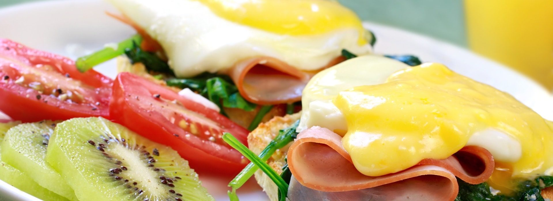 Close up view of eggs benedict with sliced tomatoes and kiwi