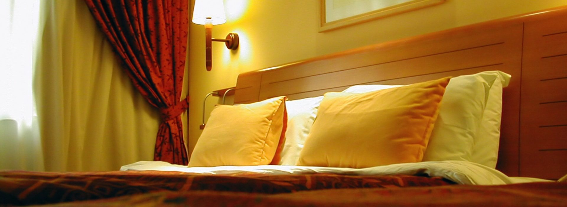 Close up view of pillows on bed leaning against headboard